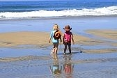 4809273-two-children-are-walking-at-the-beach-by-the-water